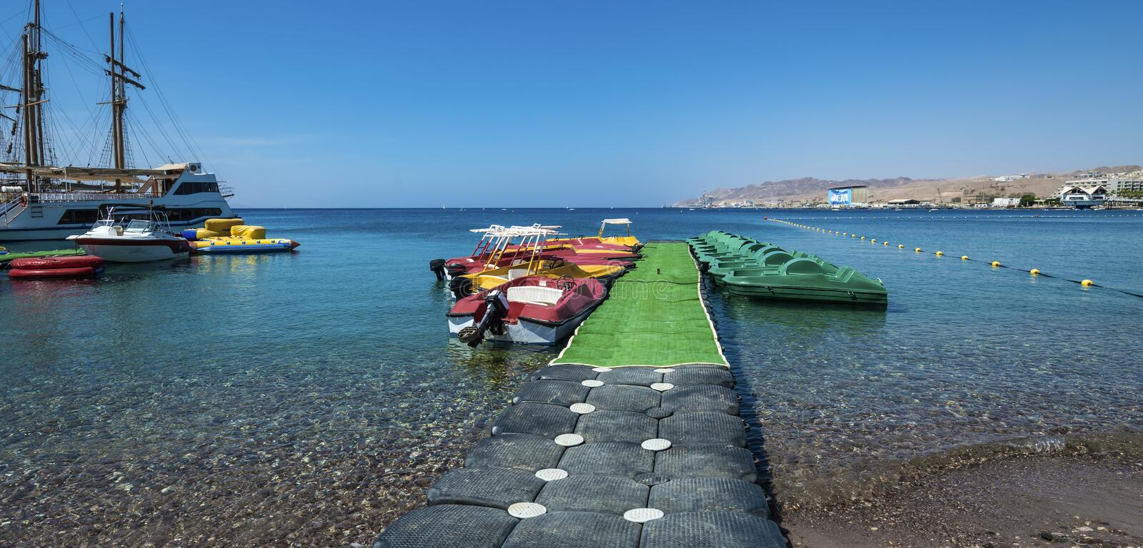 Pleasure boats in Eilat, Israel. Docked yachts and boats in the Red sea near central beach of Eilat royalty free stock photos