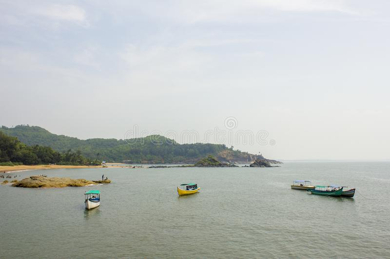 Pleasure boats in the sea near the sandy beach and green hills jungle royalty free stock images