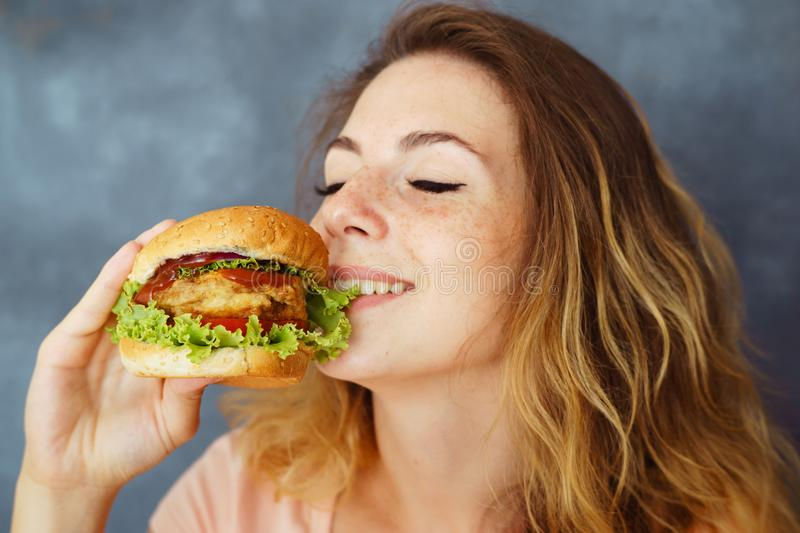 Young woman eating greedily delicious burger. Pleasure, delight, enjoyment, treat, happiness, appetite, fast food. Cute young woman eating greedily delicious stock photos