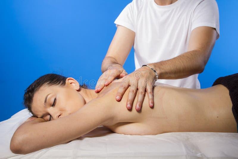 Pleasure.Masseur делая массаж на теле женщины в салоне курорта. B стоковое изображение