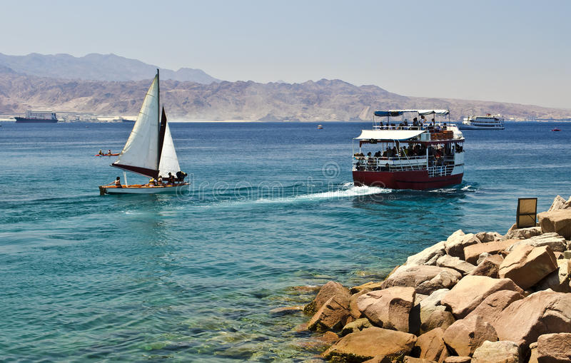 Pleasure and sport boats in gulf of Eilat, Israel. The shot was taken from northern beach of Eilat - famous resort and recreation town in Israel, Red Sea royalty free stock photos