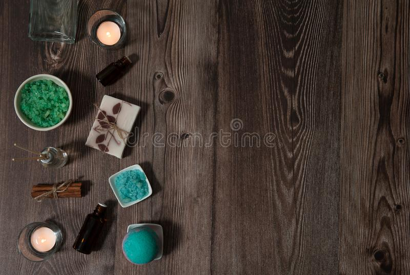 Sea salt, handmade soap, burning candles, bath bomb, small bottles of essential oils, incense sticks on a wooden background. royalty free stock photo