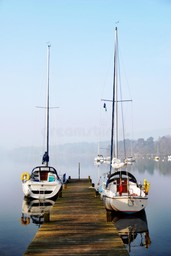 Pleasure yachts moored on rustic jetty. Two small pleasure yachts moored alongside a rustic wooden jetty with mist hanging over the water in Windermere, English stock images