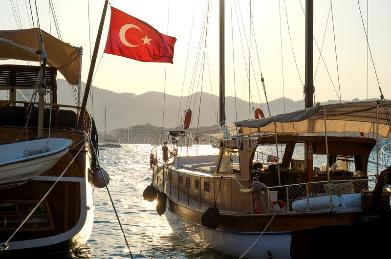 Pleasure yachts at the pier with the flag of Turkey, in backlight, Marmaris.  royalty free stock photography