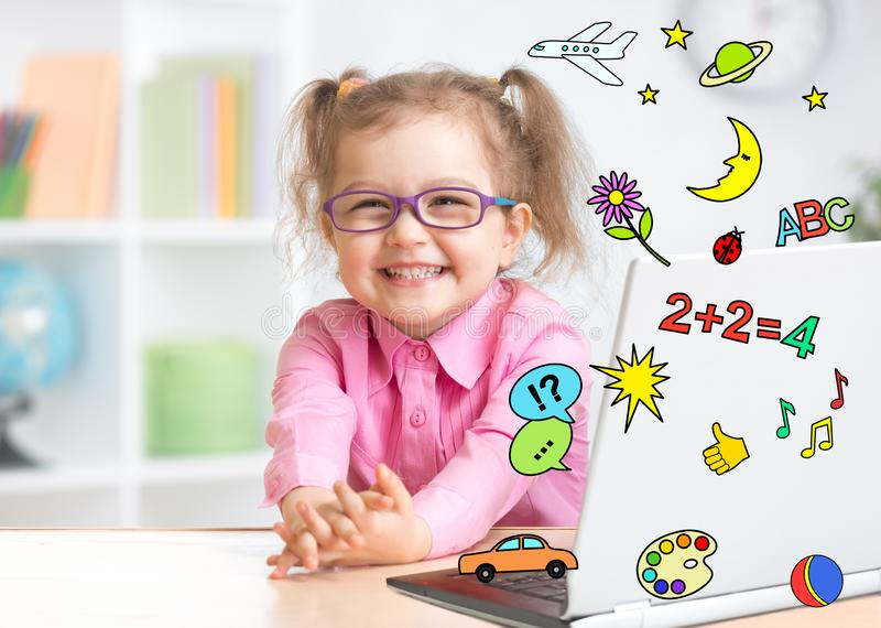 Pleasured kid using notebook actively with great interest as multimedia encyclopedia and game center stock image