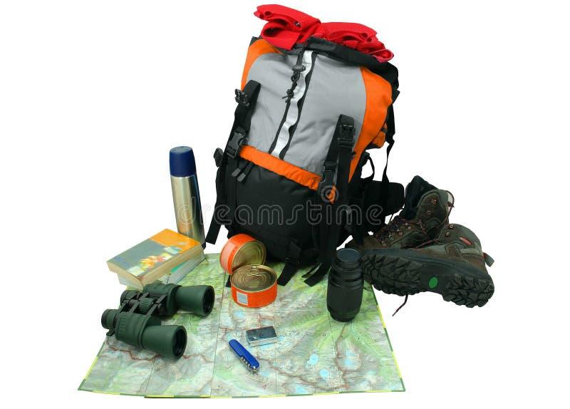 Plecak z turystycznym wyposażeniem odizolowywającym na biel zdjęcie stock