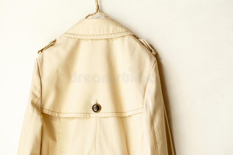 Plecy beżowy elegancki okopu żakiet odizolowywający nad bielem zdjęcie stock
