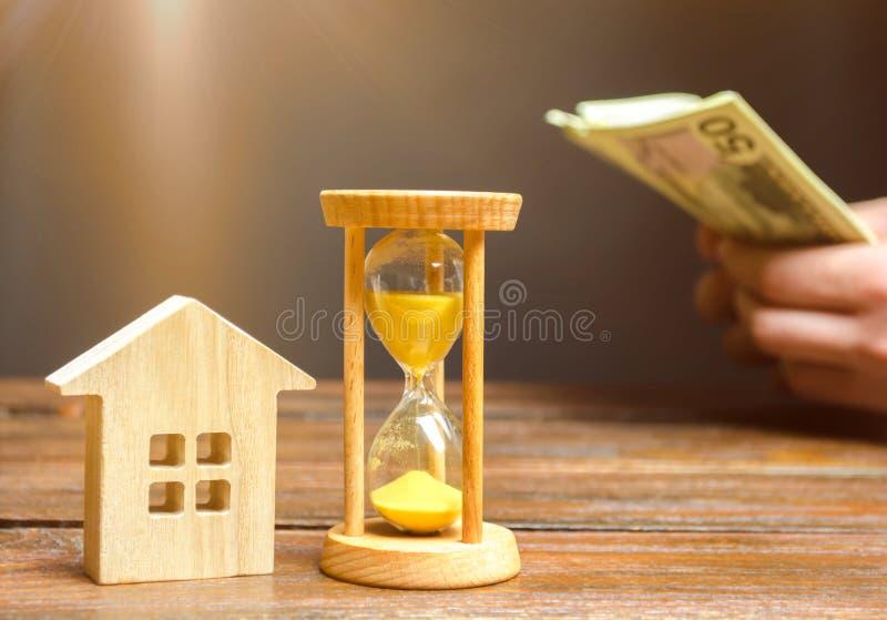 Деревянные дом и часы Бизнесмен считая деньги Оплата депозита или платы авансом для арендовать дом или квартиру Длинный стоковые фотографии rf
