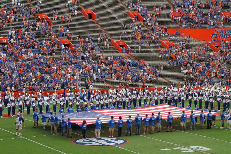 Pledge of Allegiance with a large American flag at a University of Florida football game. GAINESVILLE, FLORIDA, USA - November 21, 2015: Crowd stands for the stock image