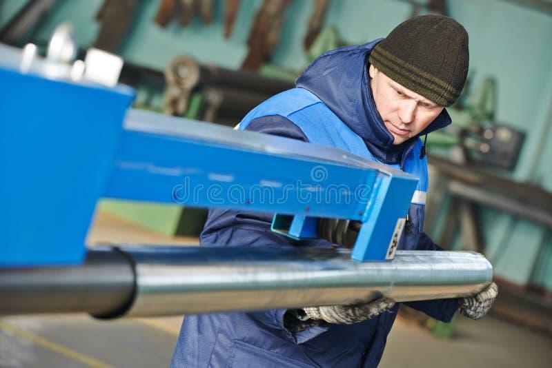 Plegamiento de la chapa trabajador industrial con el piple en la dobladora del balanceo imagen de archivo libre de regalías