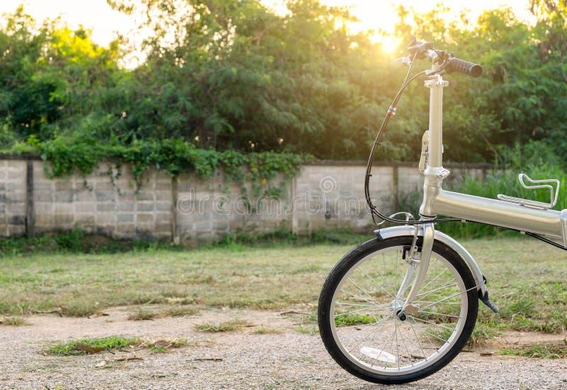 Plegamiento de la plata de la bici parqueado en fondo de la pared imagenes de archivo