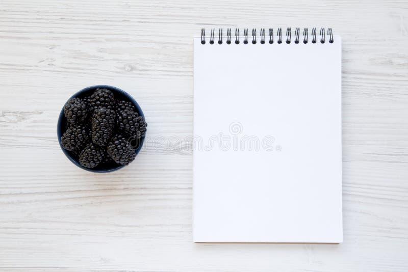 Plein bol bleu de mûres mûres avec le bloc-notes vide au-dessus de la surface en bois blanche, d'en haut Baie d'été D'en haut, aé images libres de droits