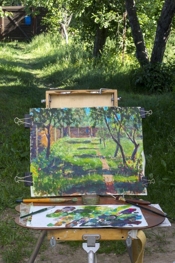 Plein luft i natur Kanfas på sketchpaden, en palett med använda målarfärger royaltyfria foton