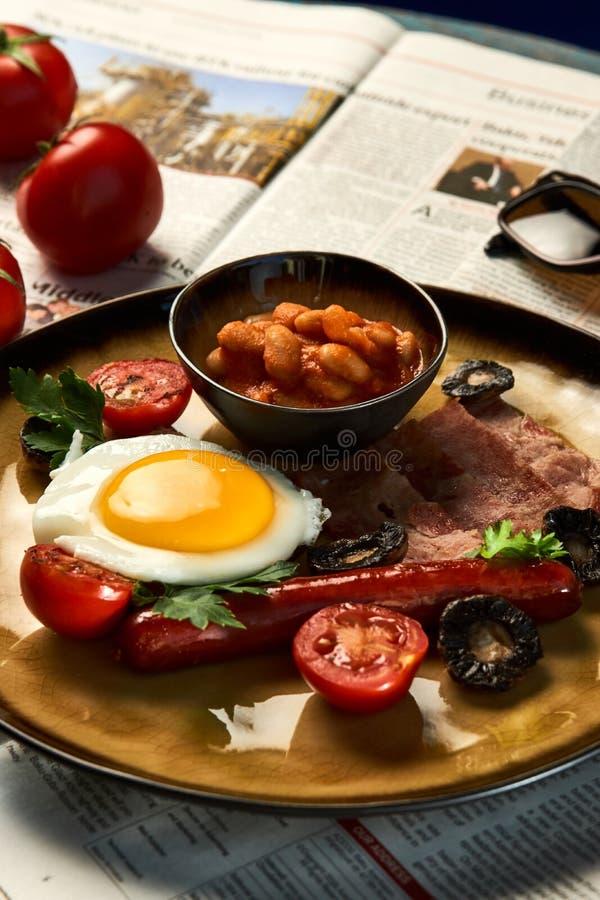 Plein petit déjeuner anglais avec le lard, saucisse, oeuf au plat, haricots cuits au four image libre de droits