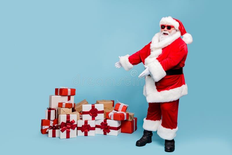Plein pied vue de son corps beau gras gai joyeux joyeux bon barbu père Noël montrant la pile de piles photos stock
