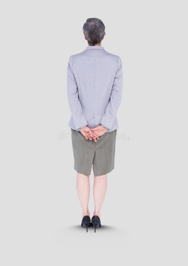 Plein portrait de corps de femme se tenant avec le fond gris photographie stock