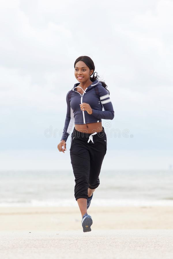 Plein portrait de corps de la jeune femme de couleur en bonne santé courant à la plage photos libres de droits