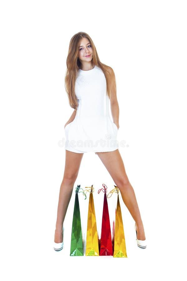 Plein portrait de jeune fille blonde de sourire avec des achats colorés photos stock