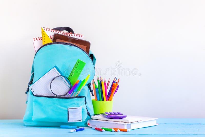 Plein sac à dos d'école de turquoise avec la papeterie sur la table image stock