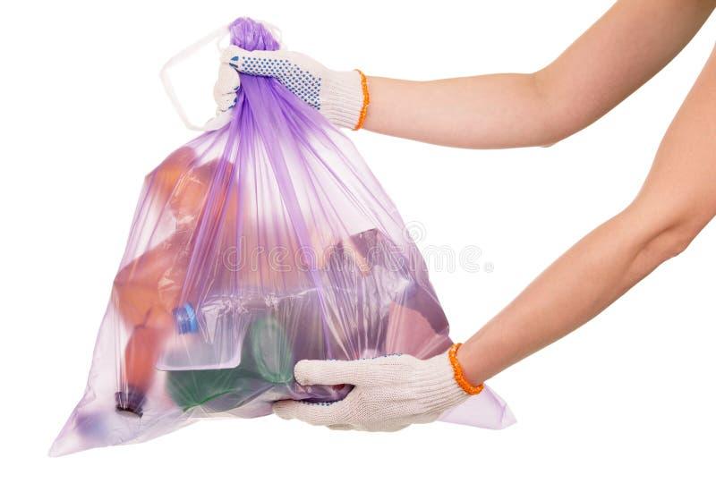 Plein sac de déchets en son plan rapproché de mains d'isolement sur le blanc image stock
