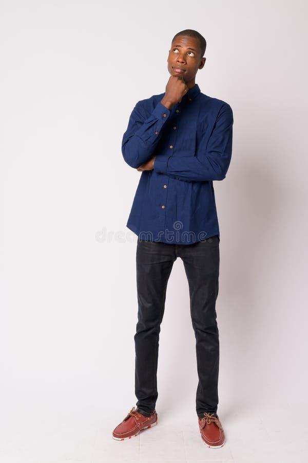 Plein tir de corps de la jeune pensée africaine chauve belle d'homme d'affaires image stock