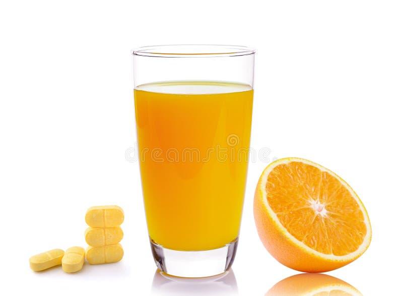Plein verre de jus d'orange et de pilules de vitamine C image libre de droits