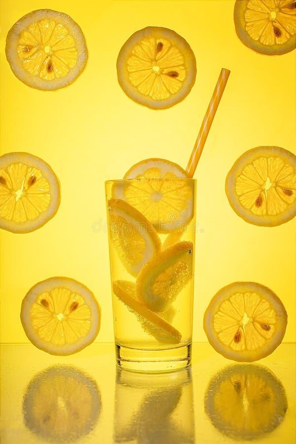Plein verre de l'eau transparente fra?che fra?che avec le citron sur le fond jaune photos stock