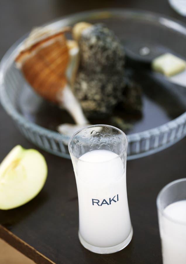 Plein verre de raki, de pomme et de fruits de mer turcs de vodka au fond photo libre de droits