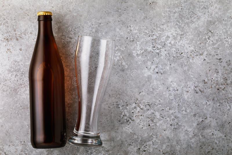 Pleine bouteille de bière et de verre vide sur la table avec l'espace de copie image libre de droits
