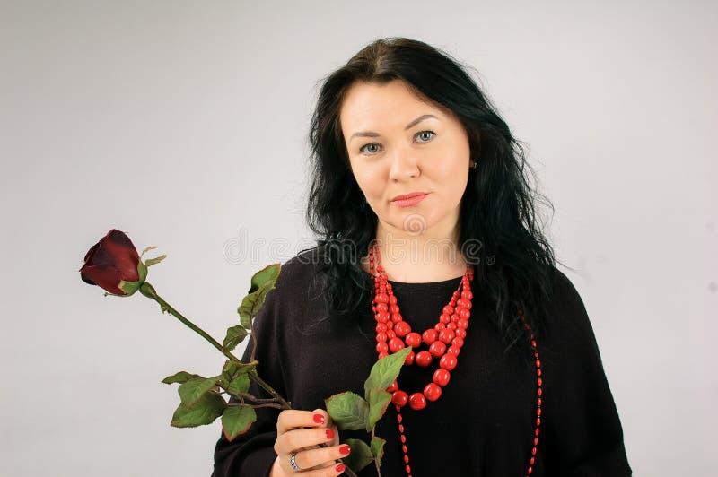 Pleine femme figure en robe noire et collier ethnique tenant Rose rouge sur Grey Background dans le studio et la regardant images libres de droits