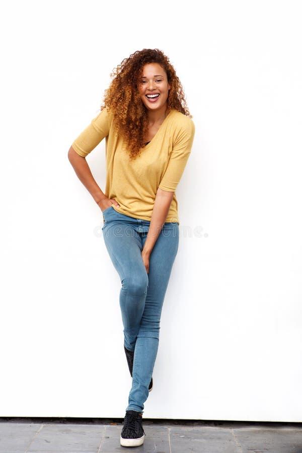Pleine jeune femme de corps avec les cheveux bouclés riant contre le mur blanc image stock