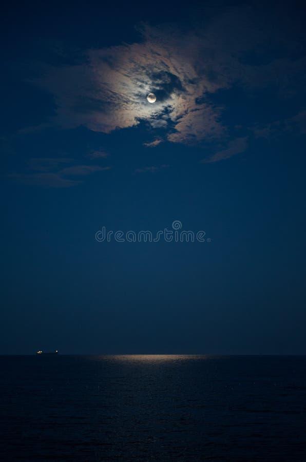 Pleine lune dans un nuage et la mer la nuit image stock