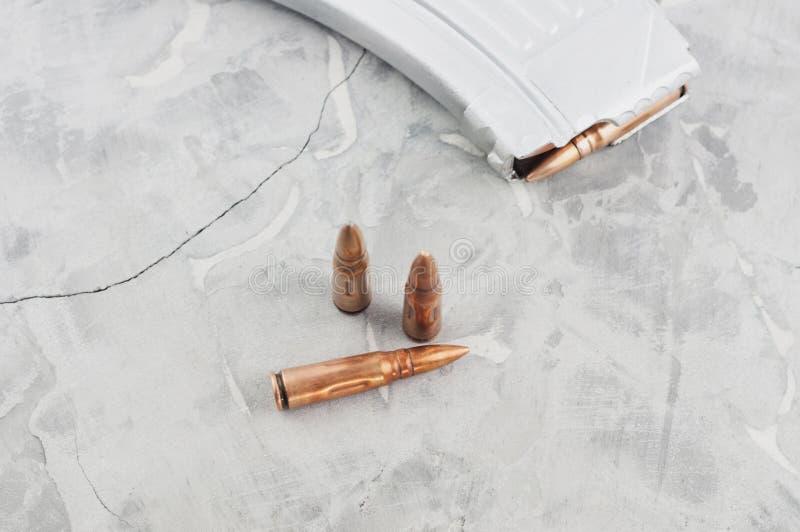 Pleine magazine argentée pour le fusil d'assaut et trois balles sur le béton cassé gris photographie stock libre de droits