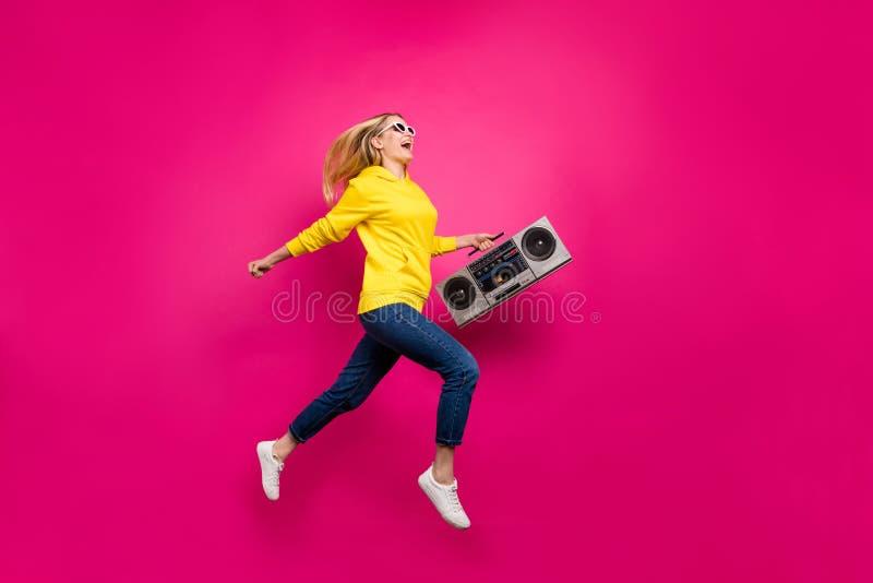 Pleine photo de corps de dame folle sautant la marche élevée au fond rose d'isolement par équipement occasionnel d'usage de parti photographie stock libre de droits