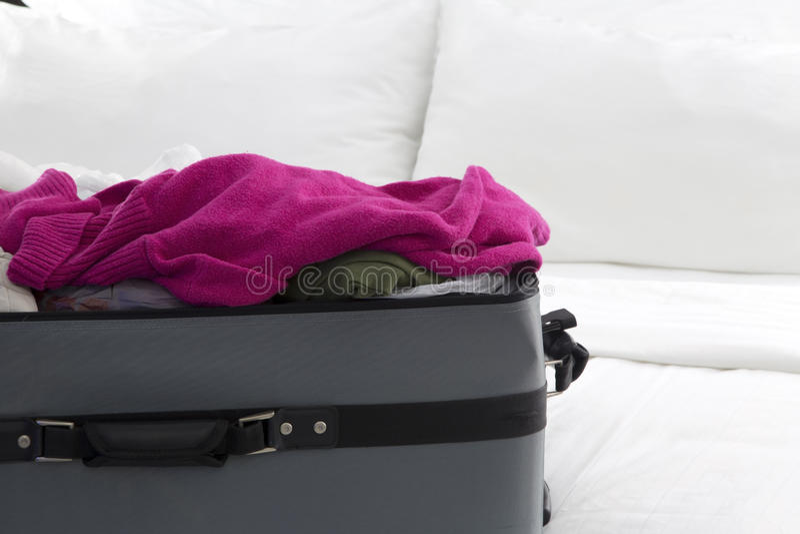 Pleine valise sur le lit image libre de droits