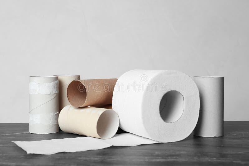 Pleins et vides petits pains de papier hygiénique sur la table images libres de droits