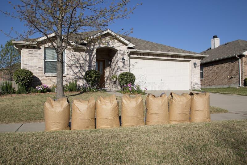 Pleins sacs de pelouse devant la maison images stock