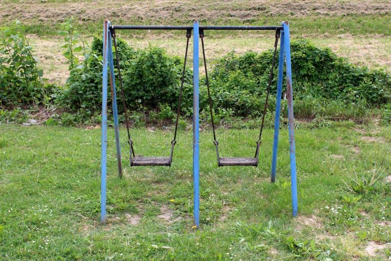 Plenerowa jawna boiska wyposażenia metalu huśtawka z rdzewiejącymi ramowymi i obdrapanymi drewnianymi siedzeniami zdjęcie stock