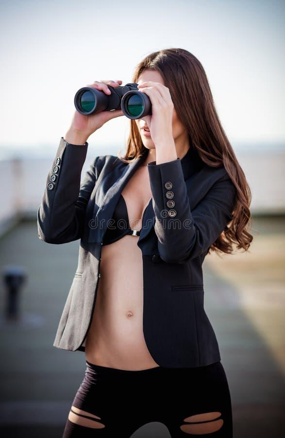 Plenerowa moda strzelająca: piękna młoda kobieta w spodniach, kurtce i staniku, trzymający lornetki w rękach fotografia stock