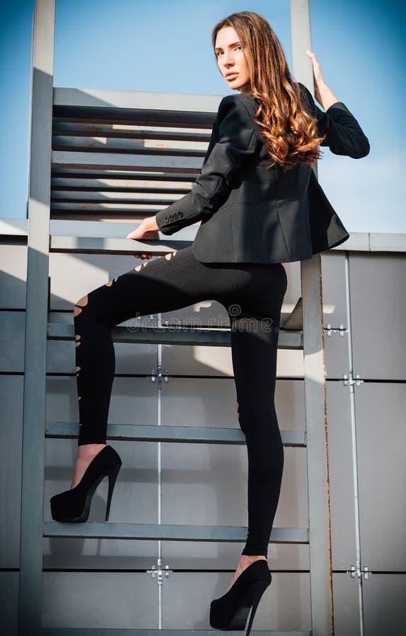 Plenerowa moda strzelająca: seksowna piękna młoda kobieta w spodniach, kurtce i butach, stoi na drabinie fotografia stock