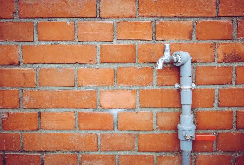 Plenerowego faucet wodny klepni?cie z szaro?ci PVC fajczan? i czerwon? klap? na czerwonej ?ciany z cegie? t?a teksturze, wodny os obraz stock