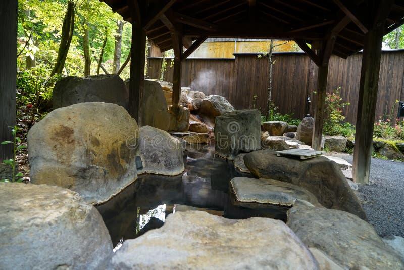 Plenerowi cieki gorącego zdroju z rockowym basenem i drewnianym filaru dachem, Kur fotografia stock