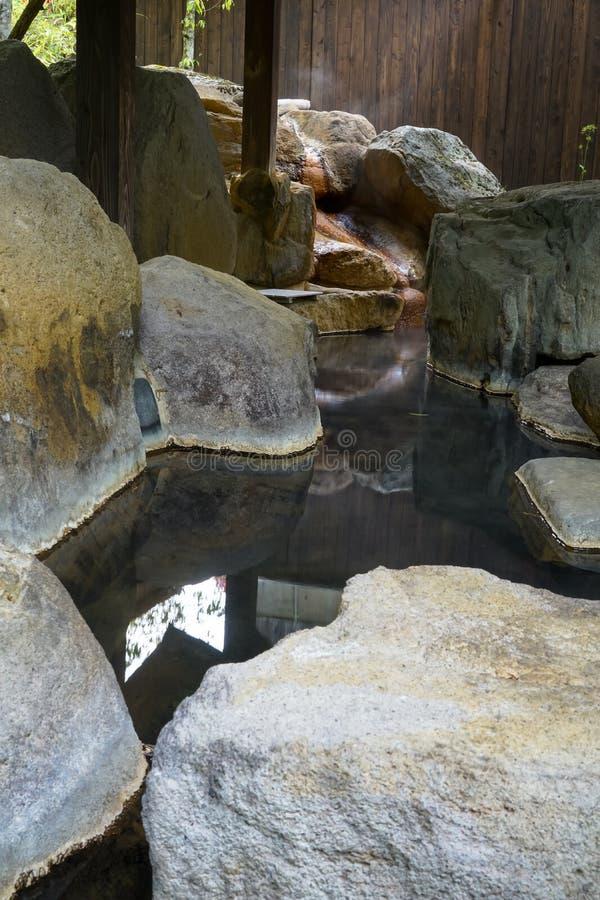 Plenerowi cieki zdroju z rockowym basenem i drewnianym filaru dachem, Kurokaw zdjęcia stock