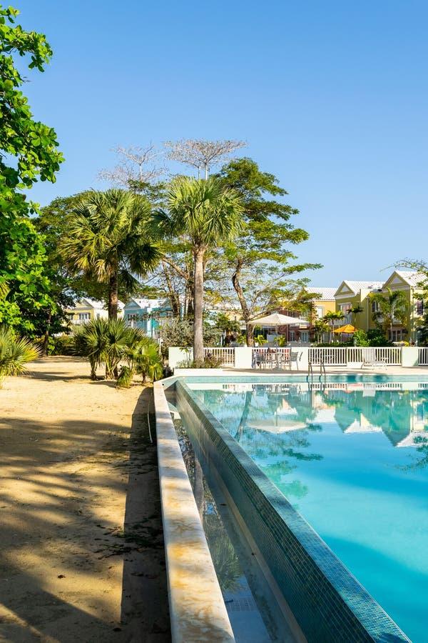 Plenerowy basen na białej piasek plaży własności nowożytny mieszkaniowy sąsiedztwo z kolorowymi grodzkimi domami, domami/ obraz stock