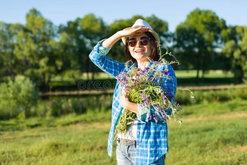 Plenerowy lato portret dorosła kobieta z bukietem wildflowers, słomiany kapelusz i okulary przeciwsłoneczni, Natury tło, wiejski  zdjęcie stock