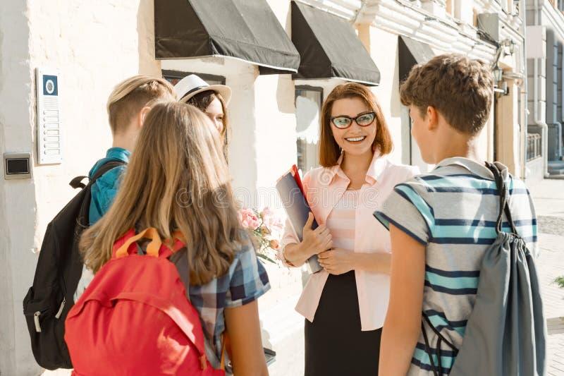 Plenerowy nauczyciel z grupą nastoletni szkoła średnia ucznie, uśmiechnięty nauczyciel opowiada dzieci fotografia royalty free
