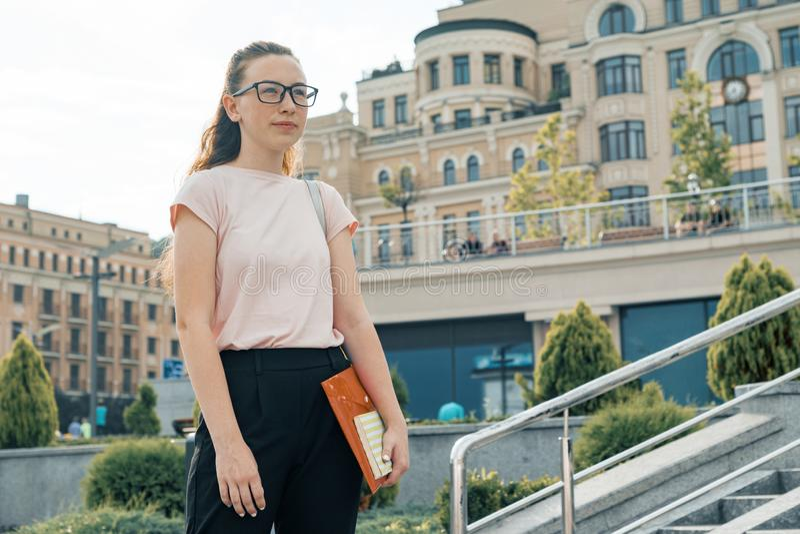 Plenerowy portret żeński uczeń 16, 17 lat Dziewczyna w szkłach, z plecakiem, podręczniki tła miasta noc ulica fotografia royalty free