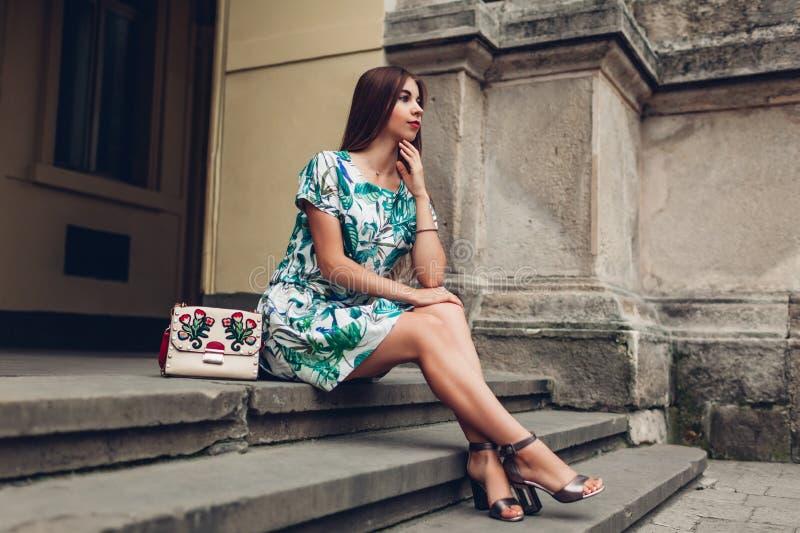 Plenerowy portret młoda piękna modna kobieta jest ubranym eleganckich akcesoria Dziewczyny obsiadanie na schodkach w mieście obraz stock