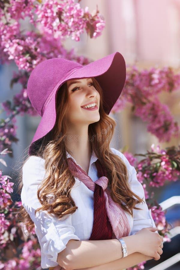 Plenerowy portret młoda piękna szczęśliwa uśmiechnięta dama pozuje blisko kwiatonośnego drzewa Wzorcowi jest ubranym eleganccy ak zdjęcia stock