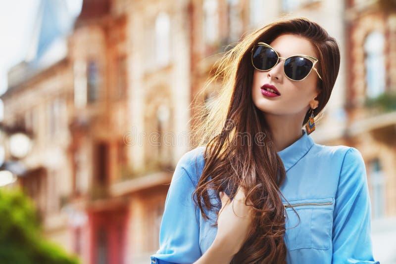 Plenerowy portret młoda piękna ufna kobieta pozuje na ulicie Wzorcowi jest ubranym eleganccy okulary przeciwsłoneczni dziewczyna obraz stock